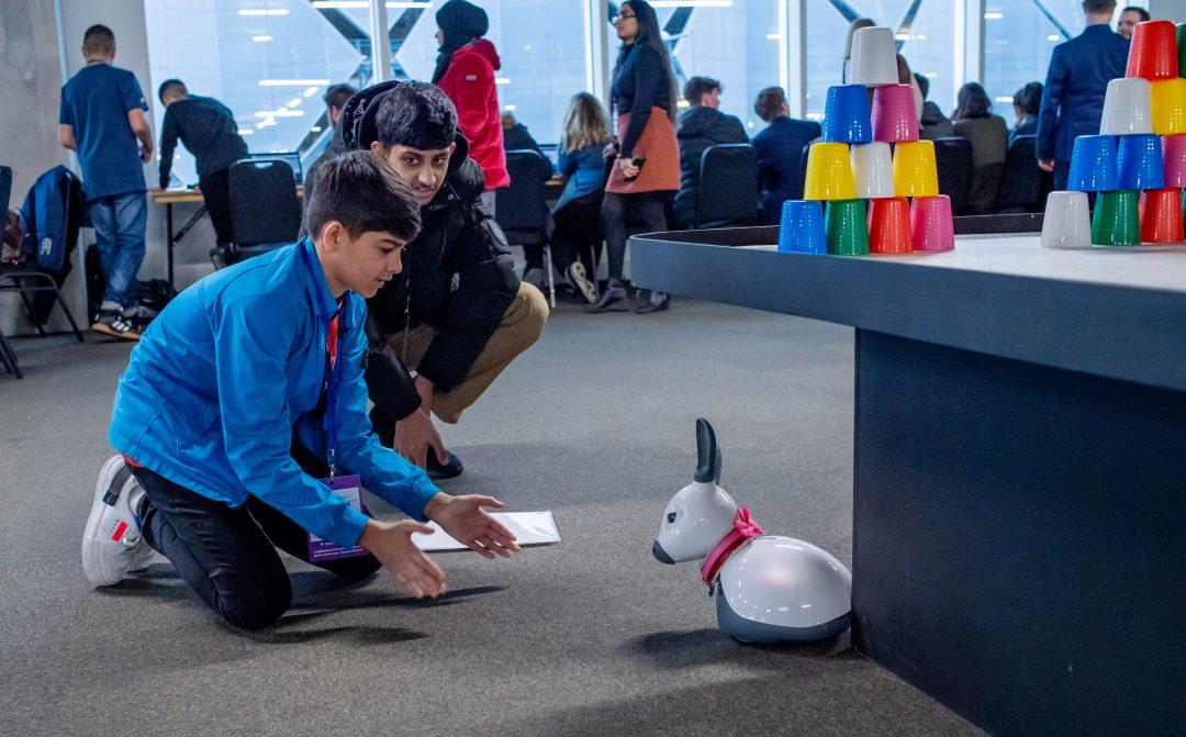Two students playing with a MiRo robot